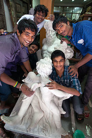 A group of workers sand and polish a marble statue at a workshop in Chor Bazaar, also known as the Thieves Market, Mumbai, In...
