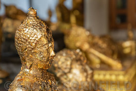 Gold leaf placed on a statue of Buddha by worshipers at the Wat Arun temple in Bangkok, Thailand.