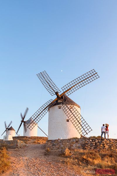 Tourist couple near windmills on the Don Quixote route, Spain