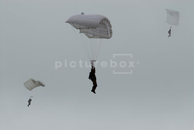 An atmospheric image of three men parachuting in.