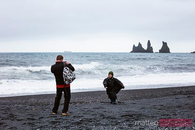 Man taking a photo of child at the beach, Vik, Iceland