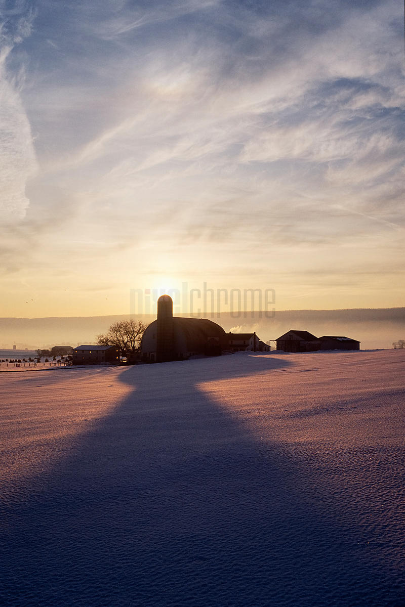 Snow Covered Field with Farm Silhouette at Sunset