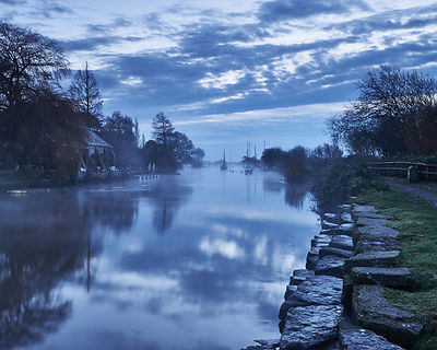 Tranquil twilight dawn scene on a cold winter morning on the misty River Frome at Wareham in Dorset