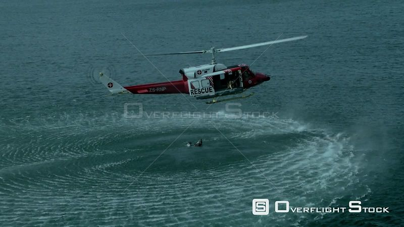 Aerial zoom in to a paramedic rescuing a man in the sea while a rescue helicopter hovers above Cape Town Western Cape South A...