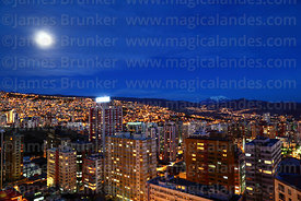 High rise buildings in Sopocachi and full moon, Mt Illimani in distance, La Paz, Bolivia