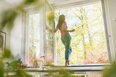 Woman standing in kitchen on windowsill