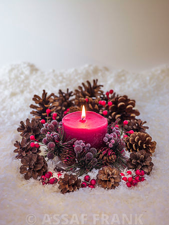 Christmas candle with pine cones in the snow