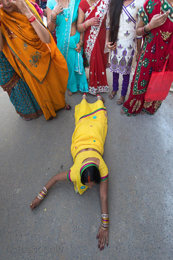 A woman prostrates herself every few steps as an exercise in religious asceticism, Assi Ghat, Varanasi, India