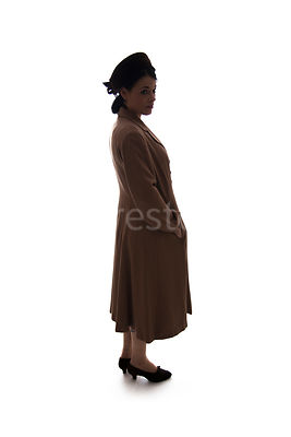 A silhouette of a 1940's woman in a hat and coat – shot from eye-level.