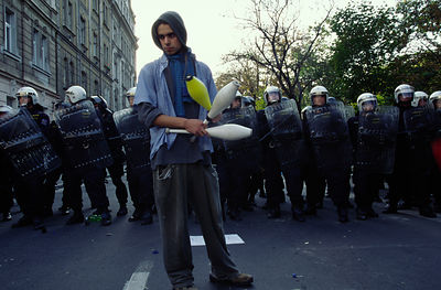 Czech Republic - Prague - A protester gets ready to juggle before a line of riot police.