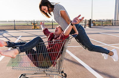 Playful young couple with shopping cart on parking level