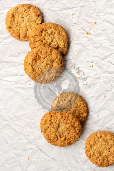 Six honey and oatmeal biscuits on a textured paper background.