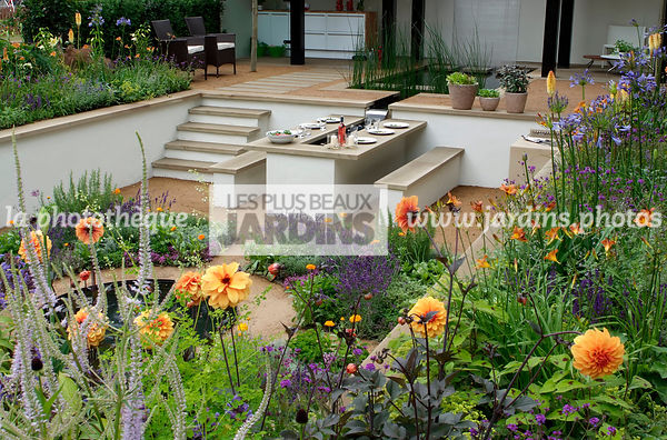 Jardin contemporain en contre-bas. Meuble de jardin : table et banc. Terrasse. Table dressée. Designer : Thomas Hoblyn Design...