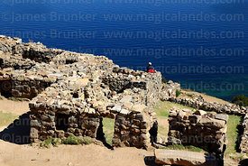 Tourist looking at view from the Chincana Inca ruins, Sun Island, Lake Titicaca, Bolivia