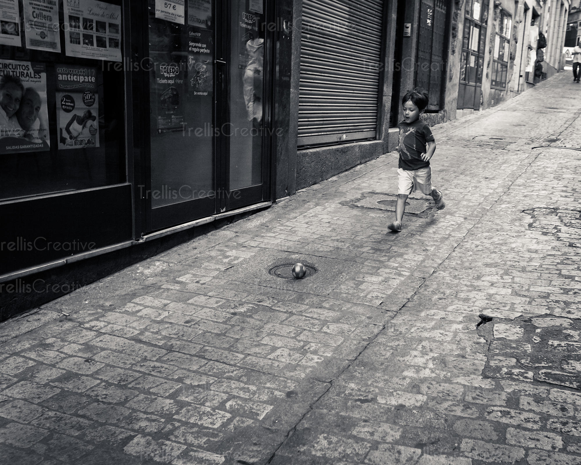 Young boy plays soccer on a cobblestone street in Spain