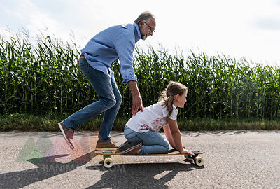 Mature man helping little girl to learn skateboarding