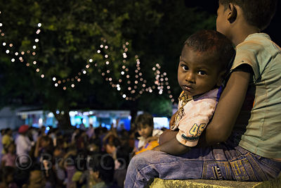 A boy watches a dance party on Chowpatty Beach during the Ganesh Chaturthi festival, Mumbai, India.
