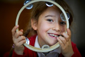 A young girl with a Tambourine at Cavendish Community Primary school