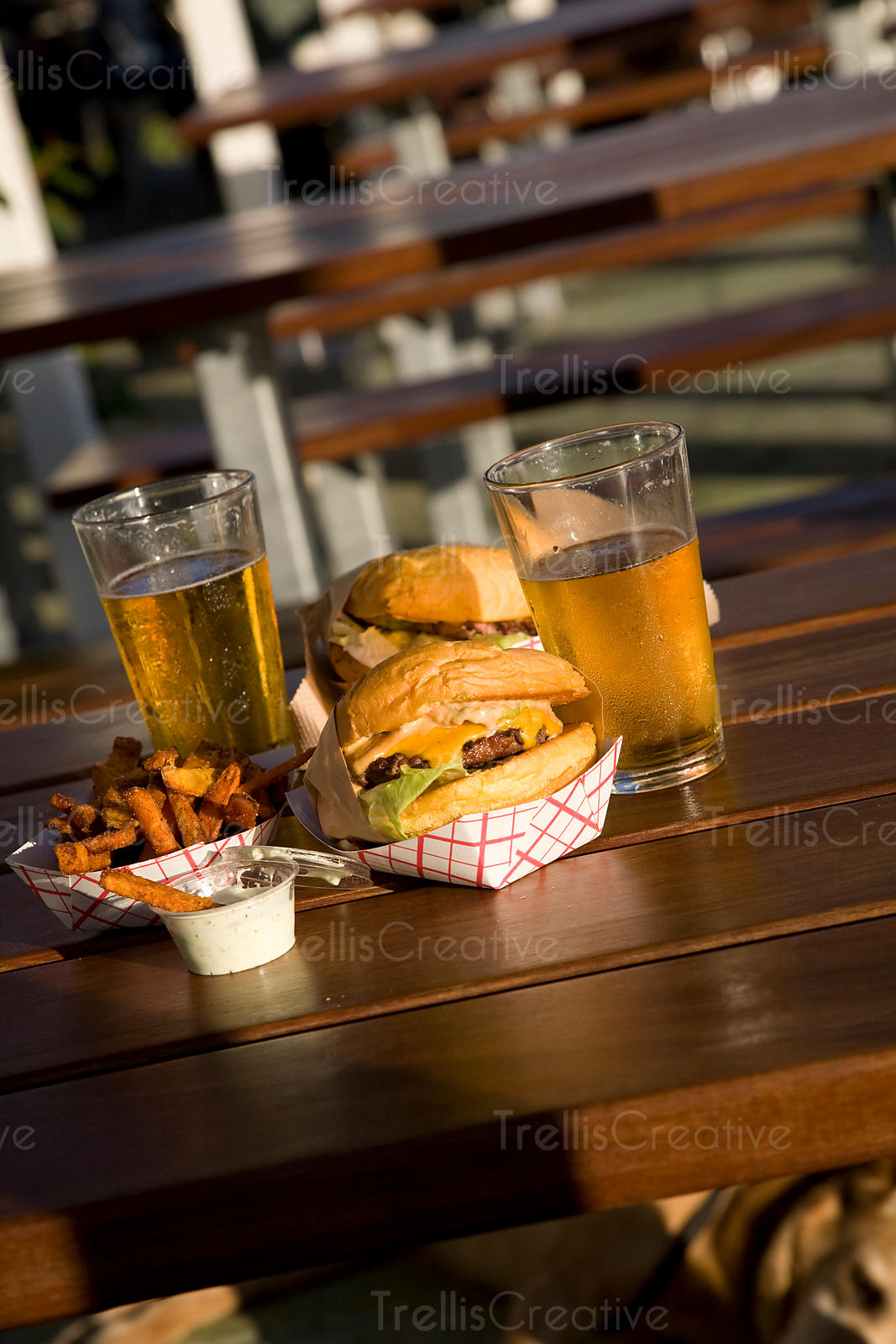 Cheeseburgers, sweet potato french fries and pints of beer on patio table