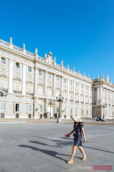 Woman walking in front of the royal palace, Madrid, Spain