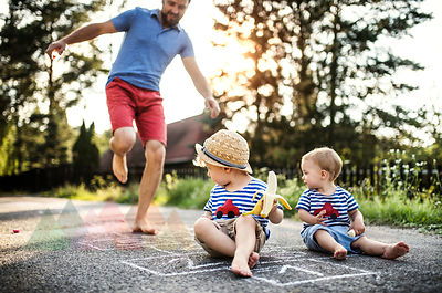 Mature man playing hopscotch while his little children watching him