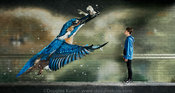 Portrait of a youth with a Kingfisher mural by the canal