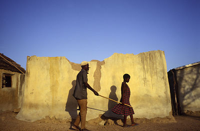 Ghana - Arigu - Anafo, a blind farmer is guided from his fields by a neighbour's child holding a stick