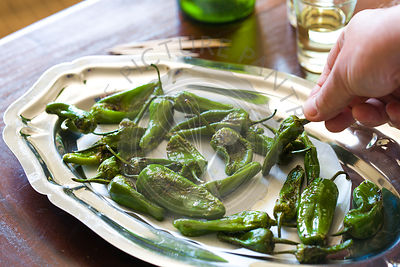padron peppers as a typical Spanish tapas style snack on wood table , with sherry glasses and bottle in background and hand h...