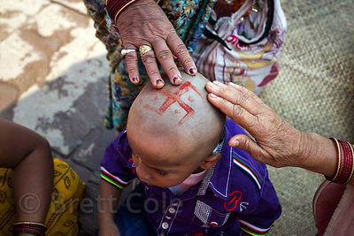 Women touch the shaved head of a boy with a swastika painted on it during prayers along the Ganges River, Varanasi, India