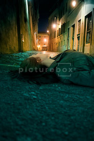 An atmospheric image of a mystery woman laying injured on the pavement of a street, n Rome, at night.