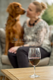 Blonde woman sitting looking at Irish Setter mix on outdoor chair with wine glass on table