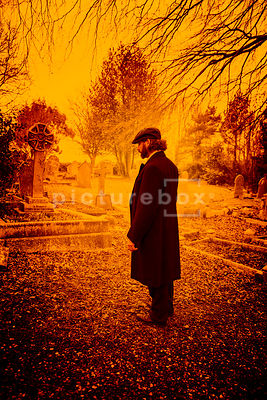 A semi-silhouette of a vintage man in a peaky cap standing in a cemetery.l.