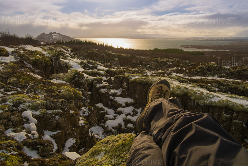 Backpacker sits atop a mountain ledge with his feet dangling off edge in Iceland