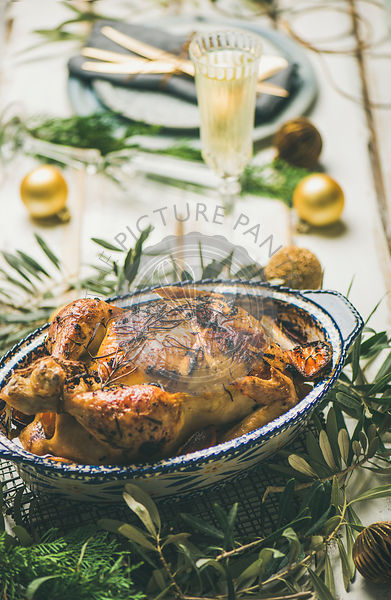 Roast chicken, plates, silverware, glass and toy holiday decoration over rustic white wooden background