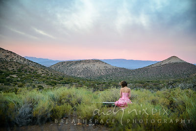 Author in a pink dress on a bench in the Karoo