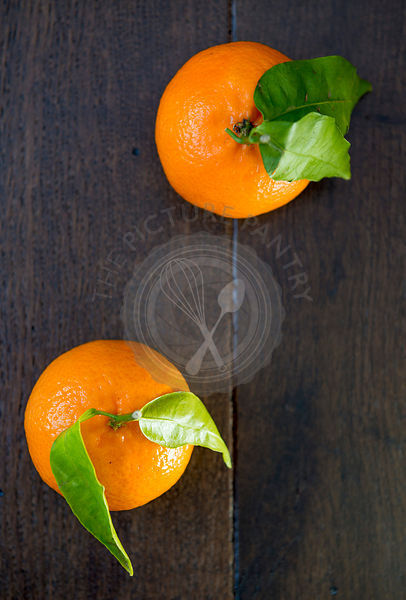 Clementine oranges on a wooden board.  North African variety of tangerine which is grown around the Mediterranean and in Sout...