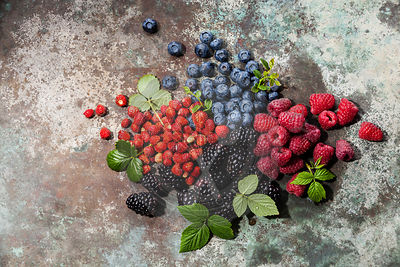 Assorted fresh berries with leaves on metal background