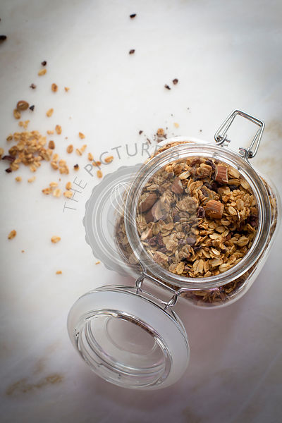 Peanut butter granola in a glass jar on a marble table on top view