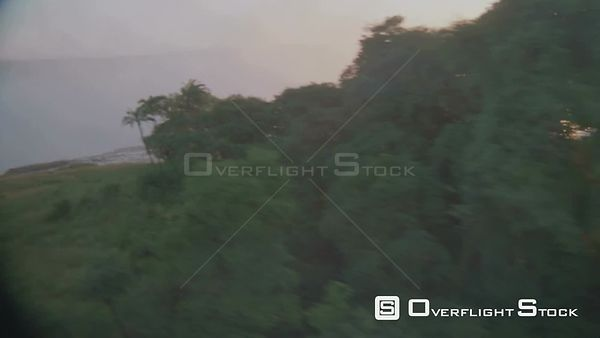 Aerial lens flare side view of riverbank behind thick vegetation to river flowing over lip, sun reflecting on mist in gorge a...