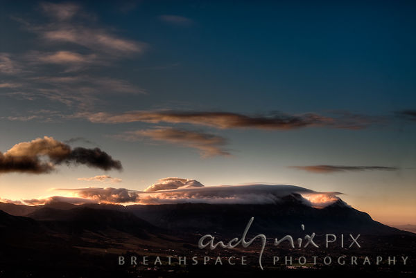 "Low pink cloud lies on top of Table Mountain at sunset, viewed from the southern ""back"" side of the mountain, Constantia and ..."