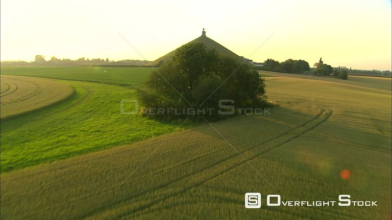 Flying over green cropland toward Lion of Waterloo monument in Waterloo, Belgium