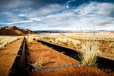 A low angle view of a an old rusted railway receding into the desert in the distance, tufts of dry veld grass growing between...