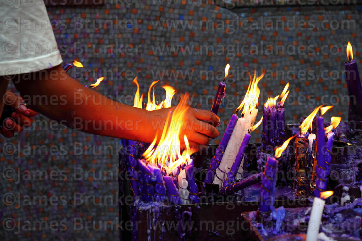 Close up of man arranging candle offerings to Señor de los Milagros in courtyard behind Las Nazarenas church, Lima, Peru