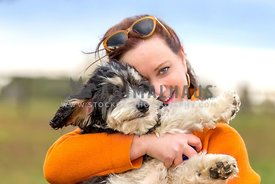wind-blown smiling woman cuddling with small dog in her arms