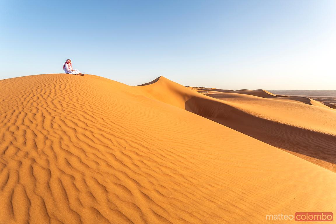 Oman, Wahiba Sands. Man with arabic dress on the sand dunes