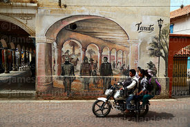 Locals on motorbike riding past mural, Tarata, Cochabamba Department, Bolivia