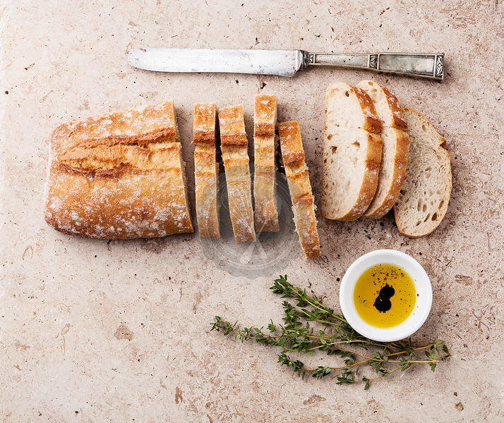 Fresh ciabatta with olive oil and thyme on stone background