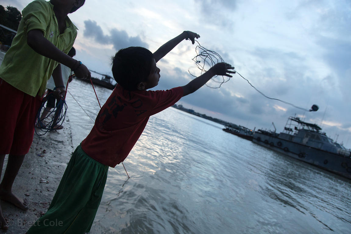 A boy casts a magnet into the Hooghly River in hopes of catching some coins left by Hindus praying in the river earlier that ...
