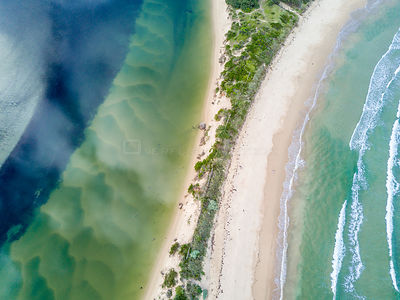 Where ocean meets river, separated by a narrow sand dune.  Aerial views  showing snd wave patterns and colours. NSW Australia