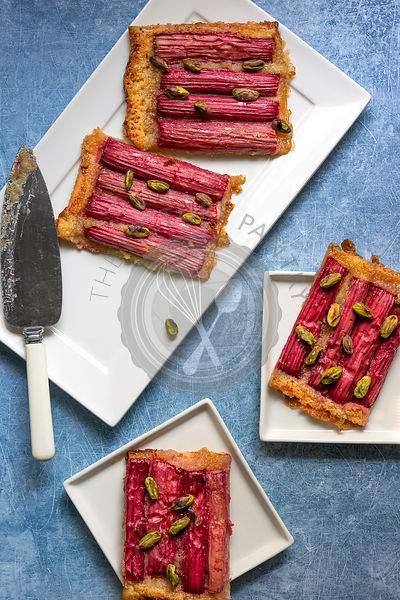 Pieces of rhubarb and pistachio tart on plates with a cake server.